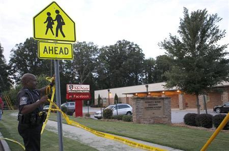 Police remove police tape after a shooting incident from the front of McNair Discovery Learning Academy in Decatur, Georgia, August 20, 2013. Police arrested a 20-year-old man on Tuesday for opening fire with an AK-47 inside an elementary school in the Atlanta suburbs, forcing the evacuation of 800 students who were all reunited with their parents without injury, officials said. REUTERS/Tami Chappell