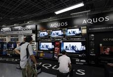 Customers look at Sharp Corp Aquos television sets displayed at an electronics store in Tokyo August 1, 2013. REUTERS/Issei Kato