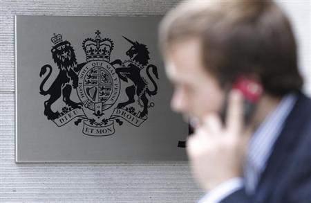 A man speaks on his phone outside a government department in London July 5, 2010. REUTERS/Luke MacGregor