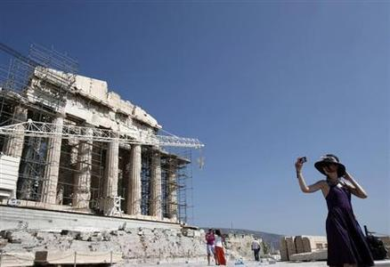 A tourist takes pictures in front of the Parthenon temple at the Acropolis hill in Athens August 19, 2013. REUTERS-John Kolesidis