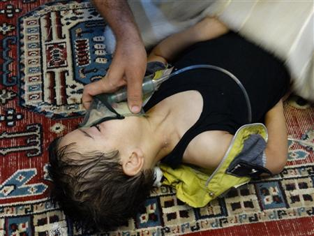 A boy, affected by what activists say is nerve gas, breathes through an oxygen mask in the Damascus suburb of Saqba, August 21, 2013 in this handout provided by Shaam News Network. REUTERS-Maher al-Zaybaq-Shaam News Network-Handout via Reuters