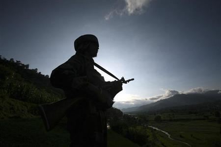 An Indian army soldier stands guard while patrolling near the Line of Control, a ceasefire line dividing Kashmir between India and Pakistan, in Poonch district August 7, 2013. REUTERS/Mukesh Gupta
