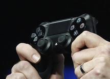 Работник Sony держит джойстик от PlayStation 4 на мероприятии в Нью-Йорке 20 февраля 2013 года. Количество предзаказов на игровую консоль PlayStation 4 компании Sony превысило 1 миллион, сообщил глава подразделения Sony SCE Эндрю Хаус на пресс-конференции в рамках престижной игровой выставки Gamescom. REUTERS/Brendan McDermid
