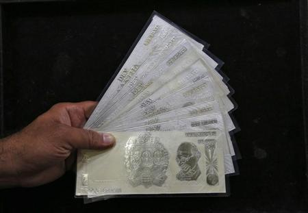 A jeweller poses with silver plates in the form of Indian rupee notes inside a showroom in New Delhi August 19, 2013. REUTERS/Mansi Thapliyal