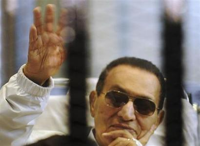 Former Egyptian President Hosni Mubarak waves to his supporters inside a cage in a courtroom at the police academy in Cairo April 13, 2013. REUTERS-Stringer