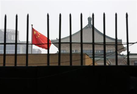 The national flag of China flutters behind a fence of the headquarters of the National Development and Reform Commission (NDRC) in Beijing, in this picture taken July 12, 2013. REUTERS/Kim Kyung-Hoon