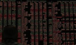 Инвестор смотрит на электронное табло, отображающее колебания фондовых рынков, в Куала-Лумпур 16 августа 2013 года. Снижение развивающихся рынков ускорилось в среду, затронув турецкую лиру, которая вместе с индийской рупией опустилась до новых рекордных минимумов на фоне ожидаемого инвесторами сворачивания усилий ФРС США по увеличению ликвидности. REUTERS/Bazuki Muhammad