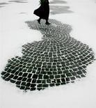Женщина пересекает Дворцовую площадь в Петербурге во время метели 21 ноября 2004 года. Жертвы семейного насилия в России ищут у государства защиты в виде специального закона. REUTERS/Alexander Demianchuk