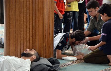 A survivor from what activists say is a gas attack vomits inside a mosque in the Duma neighbourhood of Damascus August 21, 2013. REUTERS/Bassam Khabieh