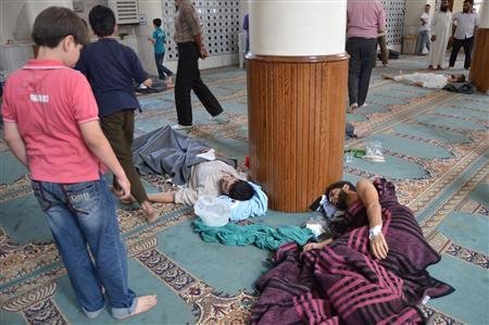 A boy looks at survivors from what activists say is a gas attack resting inside a mosque in the Duma neighbourhood of Damascus August 21, 2013. REUTERS/Bassam Khabieh