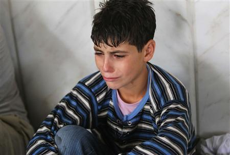 A youth who survived from what activists say is a gas attack cries as he takes shelter inside a mosque in the Duma neighbourhood of Damascus August 21, 2013. REUTERS/Mohamed Abdullah
