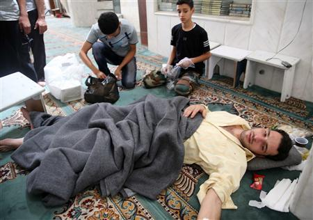 Survivors from what activists say is a gas attack take shelter inside a mosque in the Duma neighbourhood of Damascus August 21, 2013. REUTERS/Mohamed Abdullah