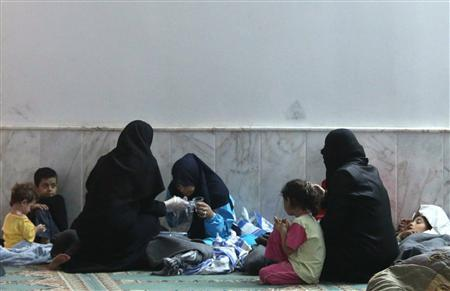 A woman who survived from what activists say is a gas attack vomits as she takes shelter with other civilians inside a mosque in the Duma neighbourhood of Damascus August 21, 2013. REUTERS/Mohamed Abdullah