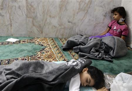 Girls who survived from what activists say is a gas attack rest inside a mosque in the Duma neighbourhood of Damascus August 21, 2013. REUTERS/Mohamed Abdullah