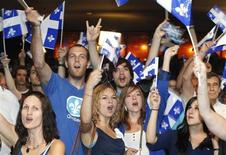 Parti Quebecois supporters cheer as they watch the results from the Quebec provincial election at the party headquarters in Montreal, September 4, 2012. REUTERS/Christinne Muschi