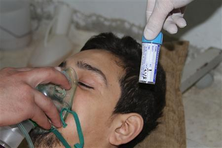 A man, affected by what activists say is nerve gas, breathes through an oxygen mask in Damascus suburbs August 21, 2013 in this picture provided by Shaam News Network. REUTERS-Fadi al-Dirani-Shaam News Network-Handout via Reuters