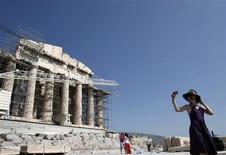 A tourist takes pictures in front of the Parthenon temple at the Acropolis hill in Athens August 19, 2013. REUTERS/John Kolesidis