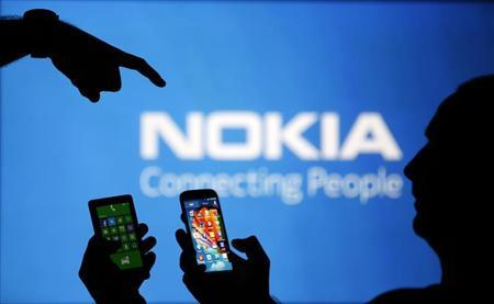 Men are silhouetted against a video screen with an Nokia logo as he poses with an Nokia Lumia 820 and Samsung S4 smartphones in this photo illustration taken in the central Bosnian town of Zenica, August 14, 2013. REUTERS/Dado Ruvic
