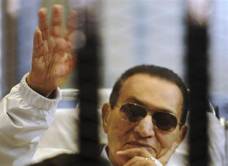 Former Egyptian President Hosni Mubarak waves to his supporters inside a cage in a courtroom at the police academy in Cairo April 13, 2013. REUTERS/Stringer/Files