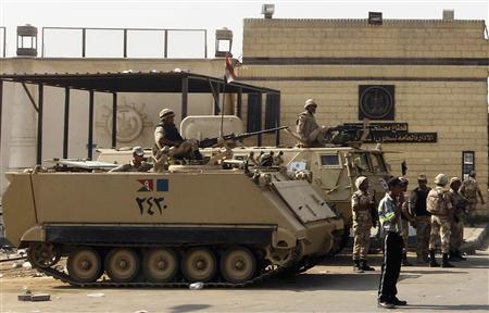 Egyptian army soldiers guard with armoured personnel carriers (APC) in front of the main gate of Torah prison where former Egyptian President Hosni Mubarak is detained in, on the outskirts of Cairo, August 21, 2013. REUTERS/Amr Abdallah Dalsh