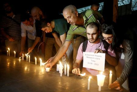 Lebanese and Syrian civilians take part in a candlelight vigil in solidarity with Syrian civilians killed by a gas attack in the suburbs of Damascus, in front of the offices of the U.N. headquarters in Beirut August 21, 2013. REUTERS/Mohamed Azakir