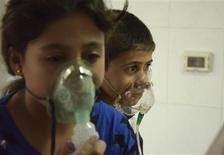 Children, affected by what activists say was a gas attack, breathe through oxygen masks in the Damascus suburb of Saqba, August 21, 2013. REUTERS/Bassam Khabieh