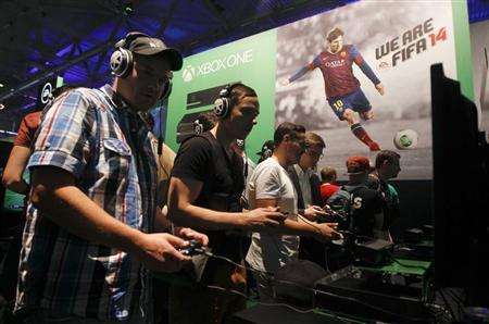 Visitors play ''FIFA 14'' with the Xbox One at the Microsoft Games exhibition stand during the Gamescom 2013 fair in Cologne August 21, 2013. REUTERS/Ina Fassbender