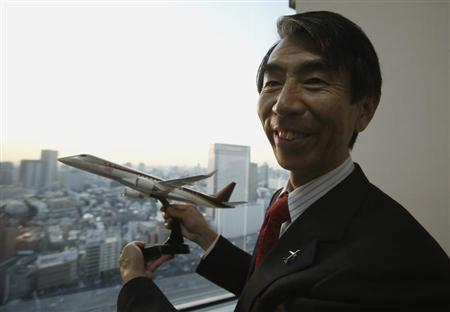Mitsubishi Aircraft Corp President Teruaki Kawai holds a model of a Mitsubishi Regional Jet (MRJ) after an interview with Reuters in Tokyo February 22, 2013. REUTERS/Yuya Shino