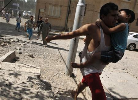A man carries a boy as he runs with other civilians to take cover after what activists said was a missile strike by Syrian Air Force fighter jets loyal to President Bashar al-Assad, in Raqqa province, eastern Syria August 21, 2013. REUTERS/Nour Fourat