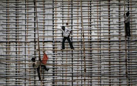 Workers install bamboo poles on a billboard under construction along a road on the outskirts of Ahmedabad May 11, 2013. REUTERS/Amit Dave/Files