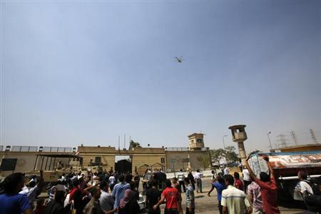 Supporters of former president Hosni Mubarak gesture as a helicopter leaves the Tora prison on the outskirts of Cairo August 22, 2013. REUTERS/Youssef Boudlal