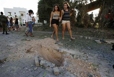 Onlookers walk past damage caused by a rocket fired from Lebanon into Israel, in Kibbutz Gesher HaZiv, near the northern city of Nahariya August 22, 2013. REUTERS-Ronen Zvulun