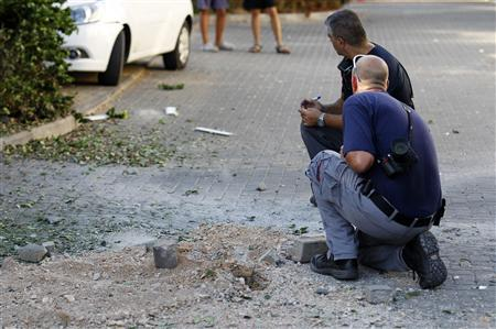 Israeli police explosive experts survey the scene next to the remnants of a rocket in Kibbutz Gesher HaZiv, near the northern city of Nahariya August 22, 2013. REUTERS-Ronen Zvulun