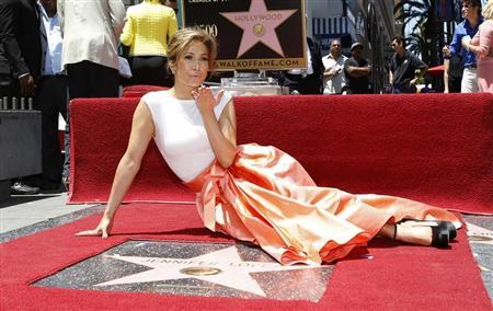 Singer and actress Jennifer Lopez blows a kiss at photographers as she poses on her star after it was unveiled on the Walk of Fame in Hollywood, California June 20, 2013 file photo. REUTERS/Mario Anzuoni