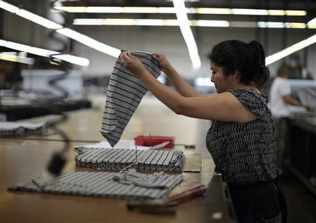 A worker cuts a clothing pattern at the Karen Kane clothing company in Los Angeles, California June 30, 2011. REUTERS/Lucy Nicholson