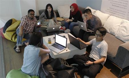A group of social media strategists chat during a meeting at an advertising agency in Jakarta March 26, 2013. REUTERS/Enny Nuraheni/Files
