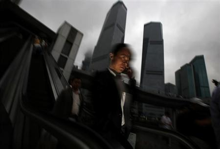 A businessman talks on his mobile phone as he walks in the financial area of Pudong in Shanghai May 30, 2013. REUTERS/Carlos Barria/Files