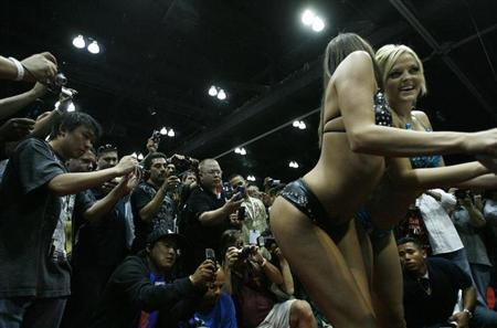 Visitors take photos and videos of two performers during the 13th annual Erotica LA (ELA) at the Convention Center in Los Angeles June 14, 2009. REUTERS/Mario Anzuoni/Files
