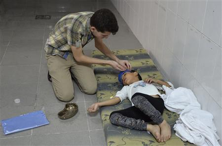A boy, affected by what activists say was a gas attack, is treated at a medical center in the Damascus suburbs of Saqba, August 21, 2013. REUTERS/Bassam Khabieh
