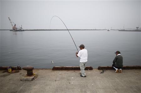 Local residents fish at Onahama port in Iwaki, about 61 km (38 miles) south of the tsunami-crippled Fukushima Daiichi nuclear power plant, Fukushima prefecture August 23, 2013. REUTERS/Issei Kato
