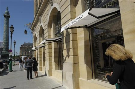 A woman walks past the LVMH's Louis Vuitton's jewellery store on Place Vendome during its opening day in Paris July 2, 2012. REUTERS/Philippe Wojazer