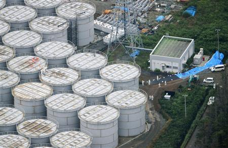 An aerial view shows workers wearing protective suits and masks working atop contaminated water storage tanks at Tokyo Electric Power Co. (TEPCO)'s tsunami-crippled Fukushima Daiichi nuclear power plant in Fukushima, in this photo taken by Kyodo August 20, 2013. REUTERS/Kyodo