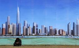 """Рабочий сидит у плаката с изображением нового делового района в пригороде Тяньцзиня 2 марта 2011 года. Называйте это новым """"китайским синдромом"""": в то время как рост крупнейшей в Азии экономики заметно замедляется, кредиты продолжают расти. Тупиковые проекты и умирающие индустрии получают большую часть новых кредитов, а более перспективным заемщикам средств не хватает. REUTERS/David Gray"""
