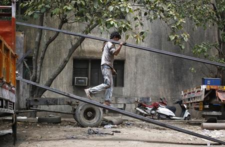 A labourer unloads an iron rod from a truck at an industrial area in New Delhi June 12, 2013. REUTERS/Anindito Mukherjee