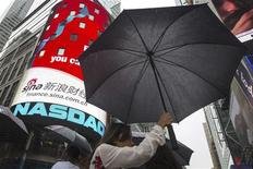 A woman holds an umbrella past the Nasdaq MarketSite in New York's Times Square, August 22, 2013. REUTERS/Lucas Jackson