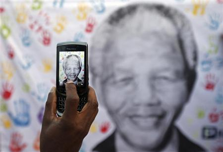 A well-wisher takes a picture using a cell phone of a banner with the image of former South African President Nelson Mandela, outside the Medi-Clinic Heart Hospital where he is being treated, in Pretoria July 18, 2013. REUTERS/Siphiwe Sibeko