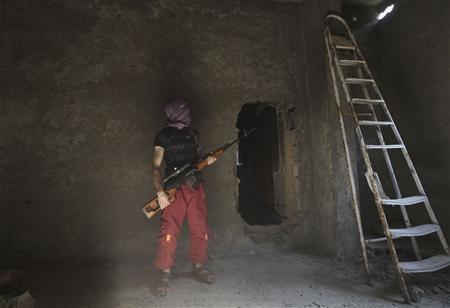 A Free Syrian Army fighter takes cover inside a house as he looks through a hole in Deir al-Zor August 23, 2013. Picture taken August 23, 2013. REUTERS/Khalil Ashawi