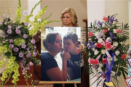 Hannah Anderson positions a photo of her mother Christina Anderson and brother Ethan Anderson on an easel at the memorial service in Guardian Angels Catholic Church in Santee, California, August 24, 2013. The two were murdered by family friend James Lee DiMaggio, before kidnapping Hannah earlier this month. Hannah was rescued and DiMaggio was killed in a shoot out with FBI agents in Idaho. REUTERS/Howard Lipin/Pool