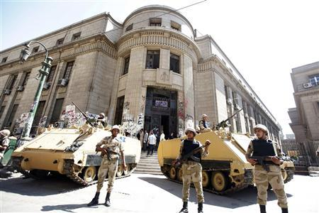 Egyptian army personnel stand guard as protesters and activists shout slogans in protest against former president Hosni Mubarak's release from prison, in front of the courthouse and the Attorney General's office in downtown Cairo August 23, 2013. REUTERS/Mohamed Abd El Ghany