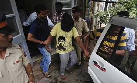 Police officers escort a man (face covered), who was arrested in connection with the gang-rape of a photo journalist, at a court in Mumbai August 25, 2013. REUTERS/Danish Siddiqui
